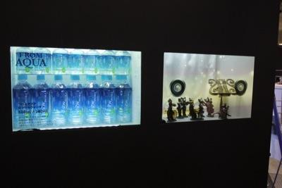 写真13 デジタルサイネージジャパンで出展されていた、後ろ側が透けて見える液晶パネル。写真だとやや分かりにくいが、ペットボトルやオーケストラの人形は後ろ側のスペースに置かれており、その前に設置されている液晶ディスプレイに文字や映像が映し出されている